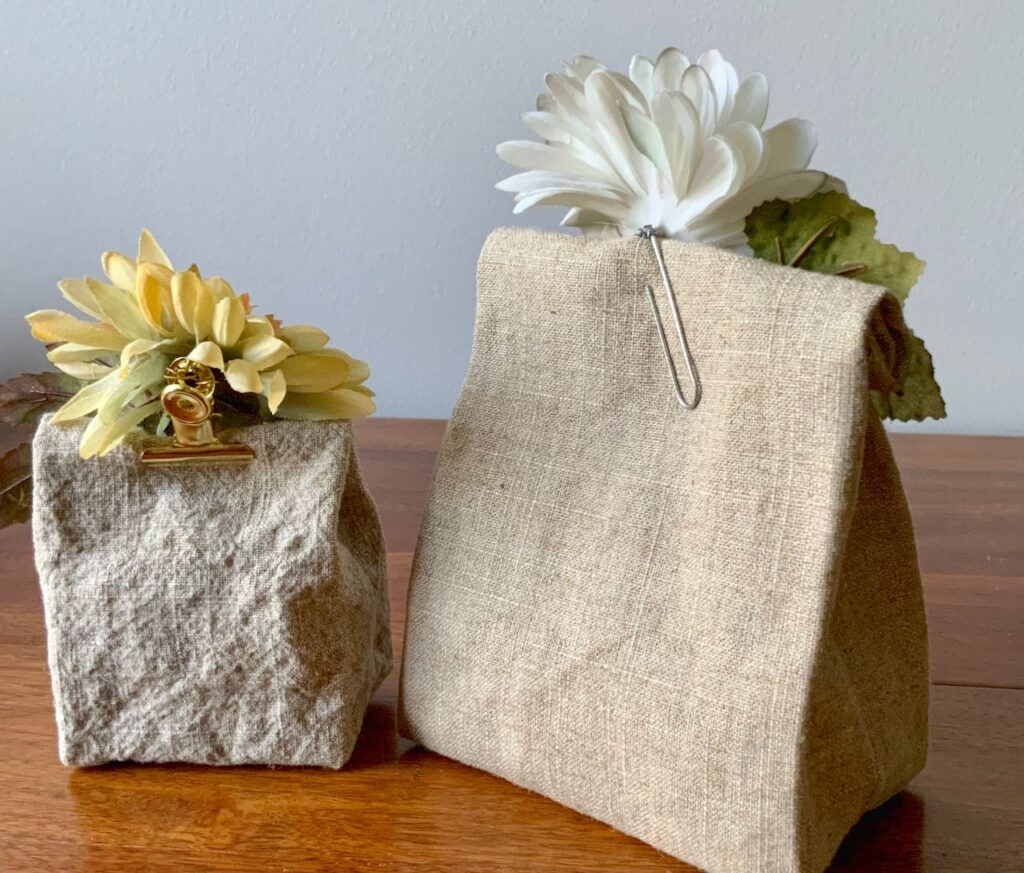 Small washed linen party favor bag and linen goody bag shown from the back with flower clips closing them