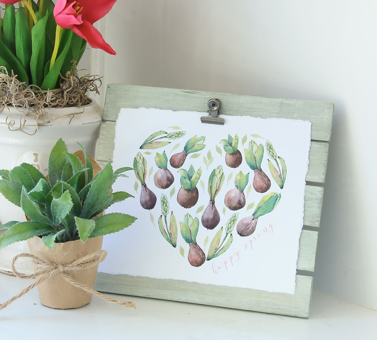 Heart shape filled with sprouting bulbs and leaves on the green washed easel