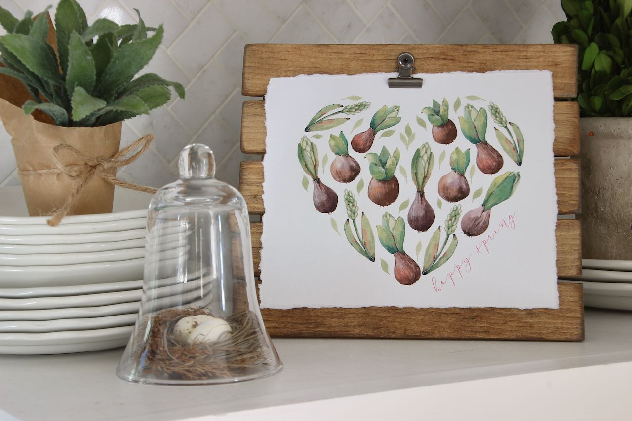 Heart shape made from sprouting bulbs and leaves clipped on a stained easel  on kitchen counter