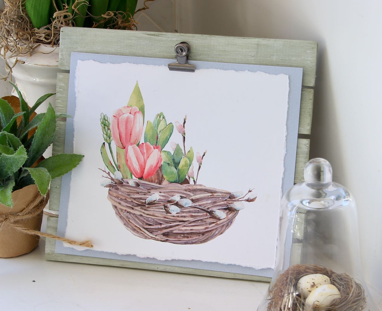 Nest with flower bulbs growing out of it on green washed easel
