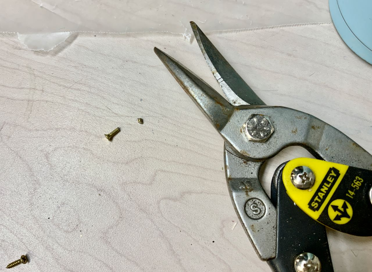 Metal Snips next to a screw head and just the tip of the screw cut off