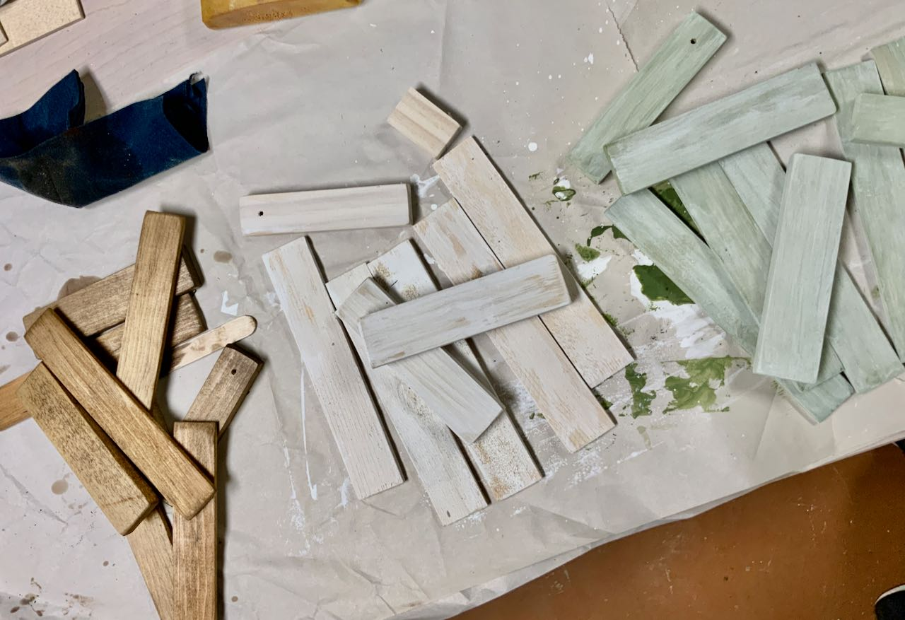 piles of wood pieces, stained brown, whitewashed and pale green