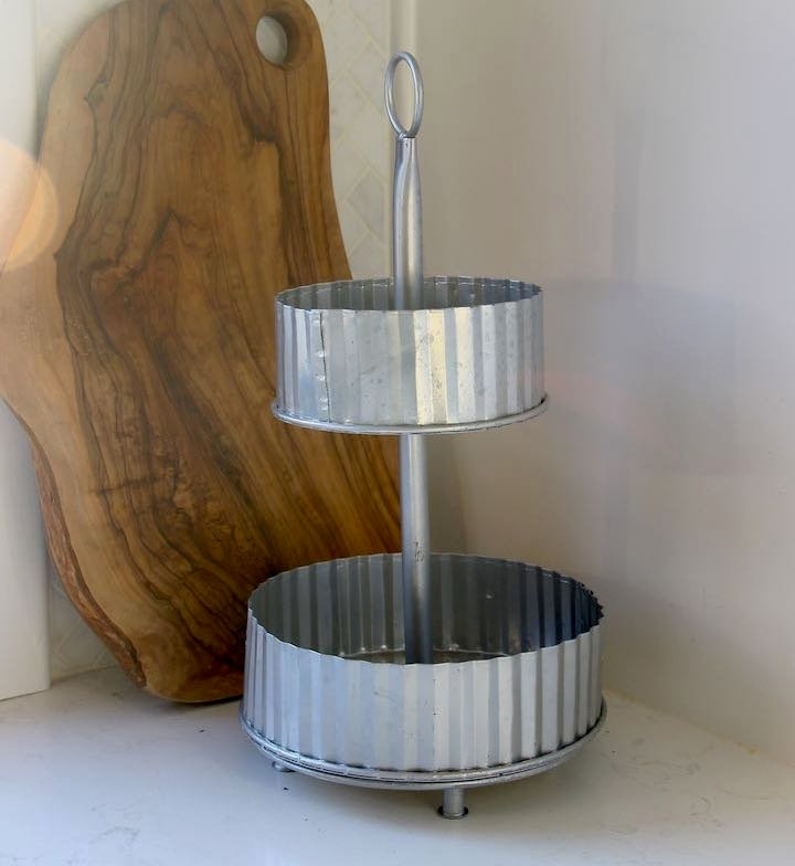 empty two-tier round galvanized tray on kitchen counter with cutting board propped behind it