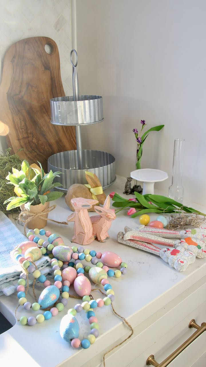 A bunch of small Easter decor and vases and plants on the kitchen counter by the tiered galvanized steel tray