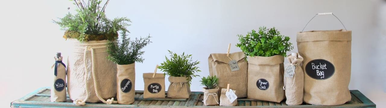 Lineup of washed linen bags and linen bags with chalk cloth labels on a long vintage shutter