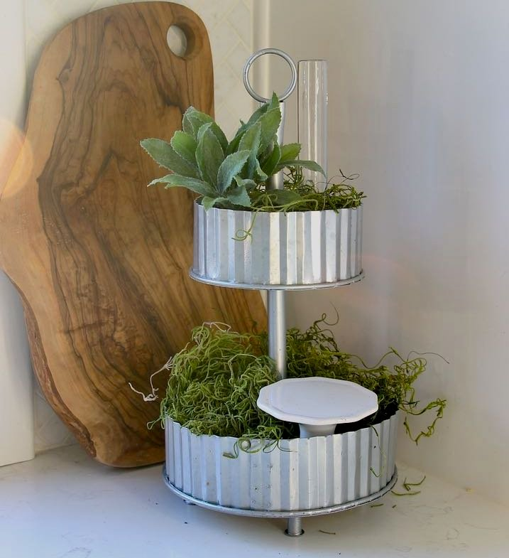 Moss filled in around the bud vase and cupcake stand to fill the tray