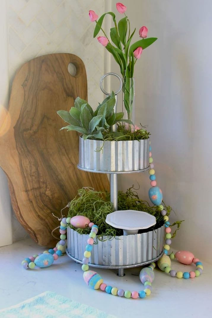 A garland of painted wooden beads and wooden eggs is on the tiered tray and pooling onto the countertop
