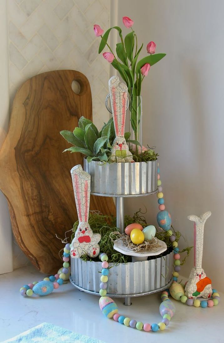 finished tiered tray with wooden Easter bunnies and garland, a nest with three painted eggsand a bud vase with Springs buds