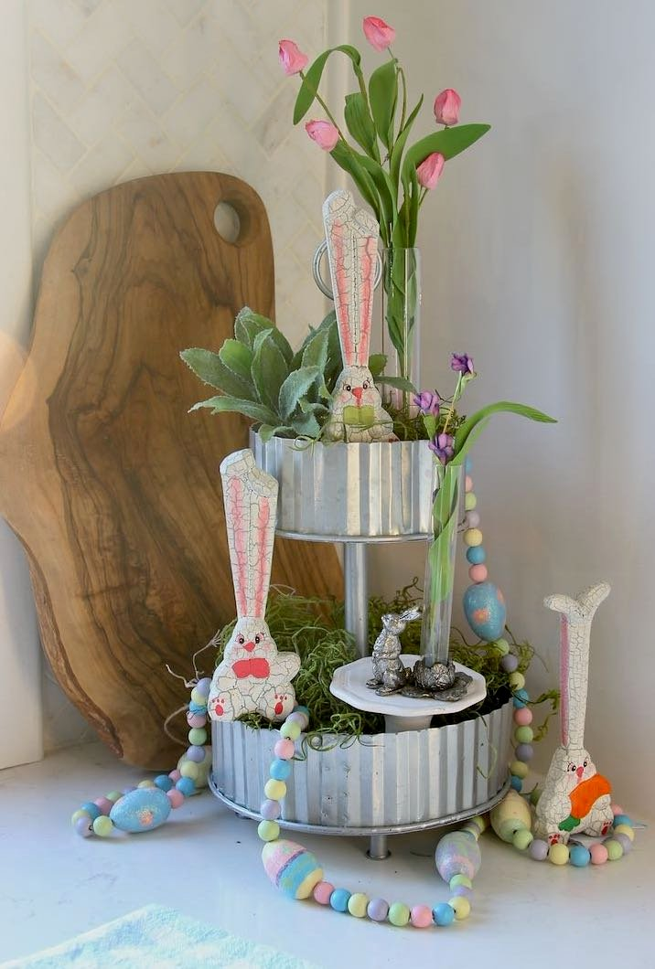 A small silver metal bunny with a clear bud vase is added to the cupcake stand on the lower tier