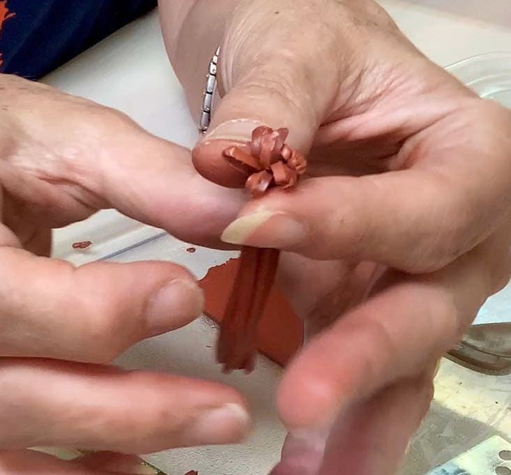 fingers spreading the ends to form a flat base